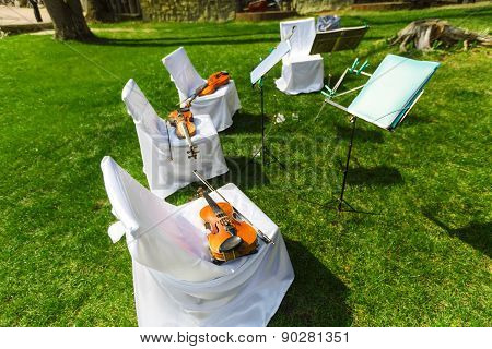 Outdoors wedding ceremony begins - string quartet's decorated festive chairs with violins stock photo