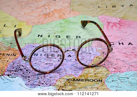 Photo of glasses on a map of Africa. Focus on Abuja. May be used as illustration for traveling theme. stock photo
