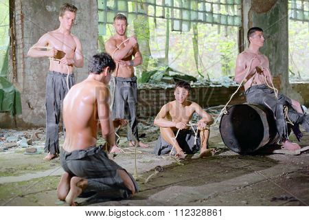 five young men in ragged pants with rope in his hands in abandoned building, focus on the left man  stock photo