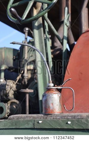 A long stemmed oil can rest on the platform of an old steam engine stock photo