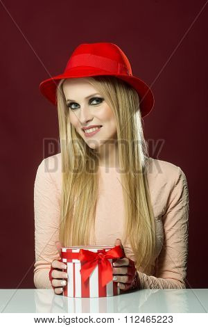 One pretty elegant sexy happy smiling young blonde woman with long hair in pink dress and red hat at white table holding roung present box for christmas valentine or new year vertical picture stock photo
