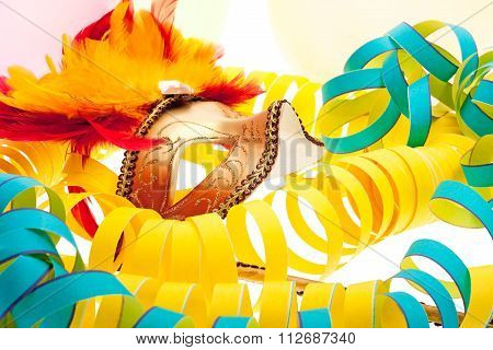 Venetian carnival mask with paper snakes and balloons in the background stock photo