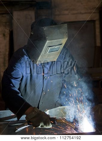 Working man with helmet shield on his head is welding steel construction. Story about weldor profession. stock photo