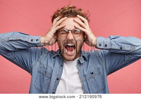Stressful Hipster Male Scremas In Panic, Closes Eyes In Terror, Keeps Hands On Head, Finds Out Terri
