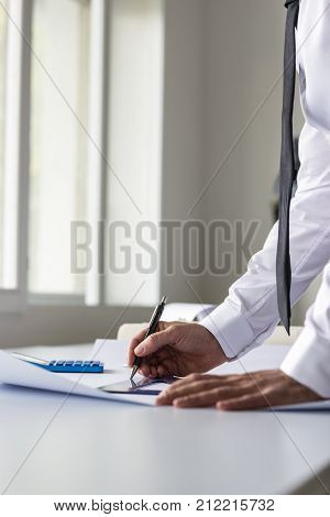 Architect designer or draftsman working with ruler and pencil in the office on a blueprint or plan in a low angle view. stock photo