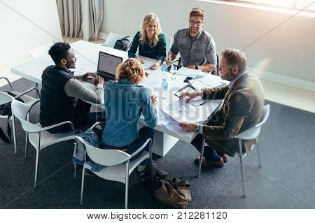 Happy working team discussing ideas on project in conference room. Group of happy business people in meeting at office.