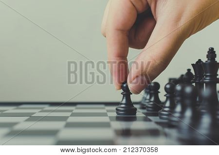 Plan leading strategy of successful business leader concept Hand of player chess board game putting black pawn Copy space for your text