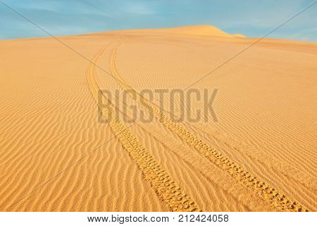 All-terrain vehicle (ATV) tracks in white sand dunes on sunrise, Mui Ne, Vietnam. Dunes around Bao Trang (White Lake, located 65 km NE of Phan Thiet) are  a major tourist attraction at Mui Ne stock photo
