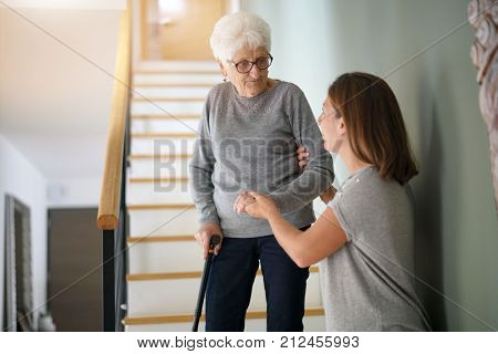 Homecare helping elderly woman going down the stairs stock photo