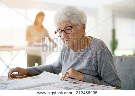 Portrait of old woman reading newspaper while homehelp irons stock photo