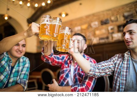 Close-up of three happy young men in casual wear toasting with beer while sitting in beer pub together stock photo