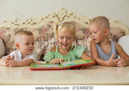 Closeup portrait of content little girl and two boys reading book and sitting at table at home. Front view.