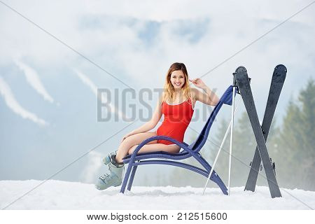 Attractive young female skier wearing red bodice sitting on a blue deck chair near skis and poles at ski resort. Foggy mountains and forest on the background. Ski season and winter sports concept stock photo