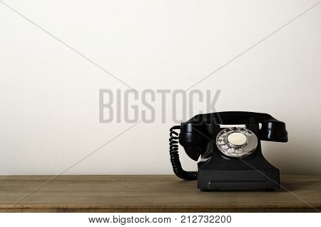 Black 1940s vintage bakelite telephone at eye level on a wooden desk with ivory white wall as background providing copy space to the left. stock photo