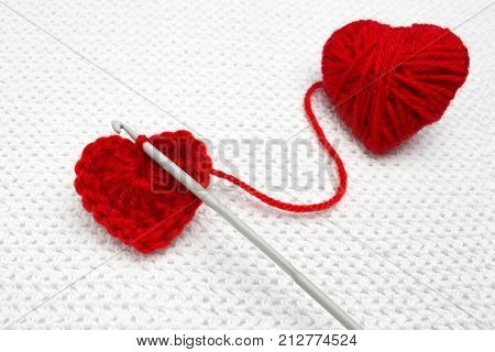 Old metal crocheting hook and red yarn ball like a heart on the white crochet background. A handmade crocheted wool organic red heart. Red heart made of wool yarn and crochet heart. Soft focus stock photo
