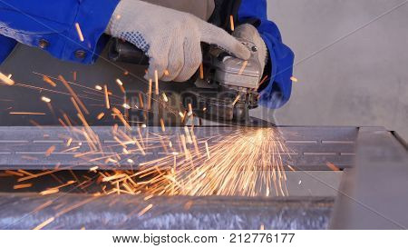 Electric wheel grinding on steel structure in factory Low speed shutter. Employee work with metal or aluminium using special production equipment. Portrait of a worker grinding a metal plate. Industry stock photo