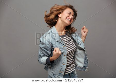 Portrait of a satisfied cheerful teenage girl dressed in denim jacket celebrating success while danc