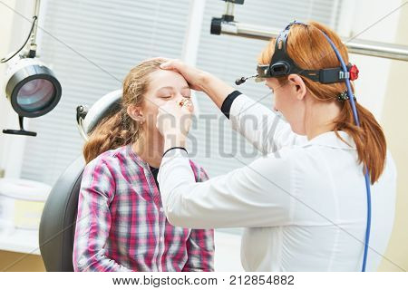 female doctor of ENT ear nose throat at work examining girl nose stock photo