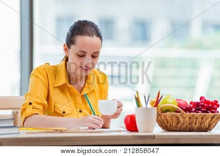 Young school gilr drawing pictures at home stock photo