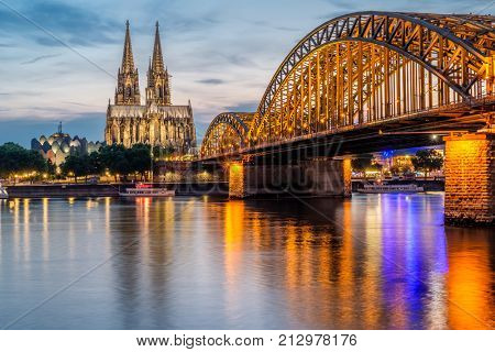 Night View of Cologne Cathedral (Kolner Dom) and Rhine river under the Hohenzollern Bridge, Cologne city skyline at night, North Rhine Westphalia region, Germany. stock photo