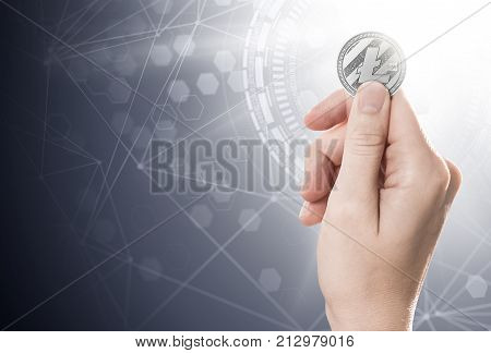 Hand holding a Litecoin on a bright background with blockchain network. Copy space included. Illustration stock photo