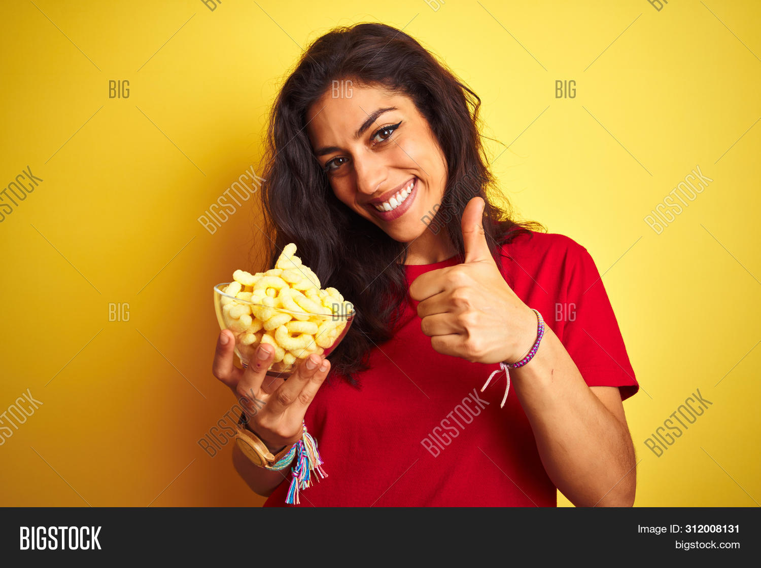 Young beautiful woman holding bowl with extruded corn over isolated yellow background happy with big
