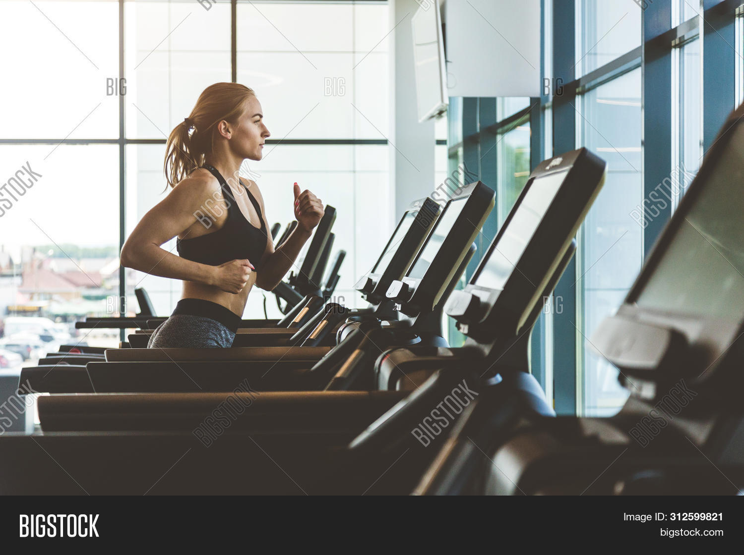 The Athletic Woman Dressed In A Black Sportswear Running On The Treadmill In The Modern Gym