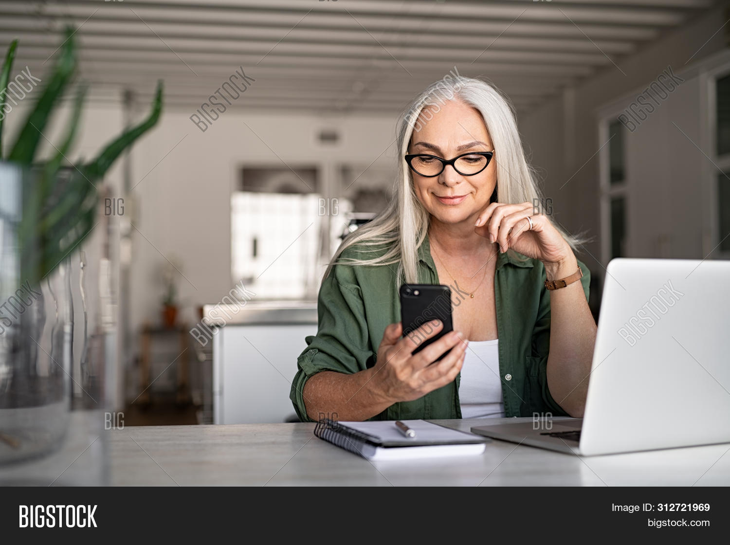 Happy senior woman using mobile phone while working at home with laptop. Smiling cool old woman wear
