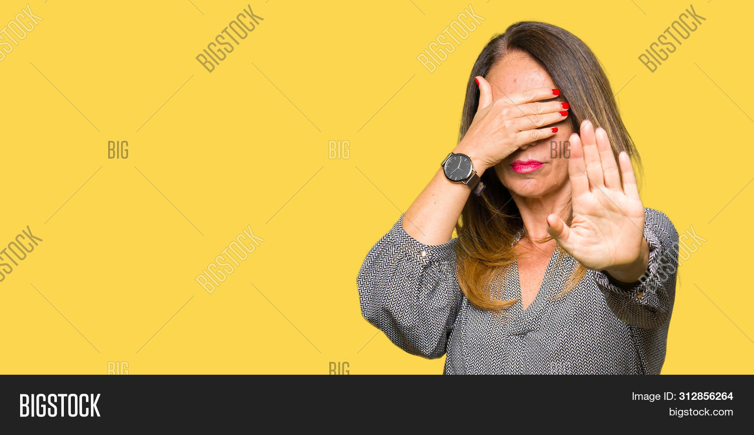 Beautiful middle age business woman covering eyes with hands and doing stop gesture with sad and fea