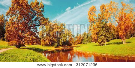 Autumn landscape scene - autumn trees near the river in sunny October park lit by sunlight. Panorama of autumn park in sunny weather, vintage filter applied