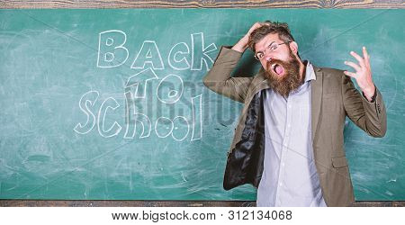 Teacher or educator stands near chalkboard with inscription back to school. Teacher unhappy shouting hysterically face. Man refuses begin work at school. Hate school. Teacher goes mad about schooling stock photo