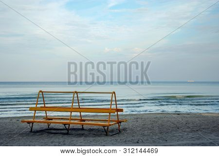 Lonely orange bench on the shore of a calm blue sea with a ship on the horizon. The sky is gray with clouds. There are small waves near the shore. On the shore of the sand. stock photo