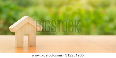 A wooden house stands on a nature green background. Affordable housing, credit and loans. The concept of buying and selling real estate, renting. Search for a house. Investments. Copy space. Banner stock photo