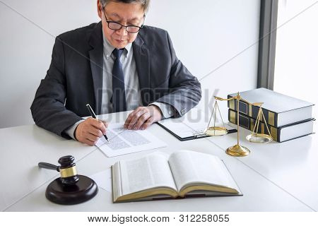 Judge gavel with Justice lawyers, Counselor in suit or lawyer working on a documents in courtroom, Legal law, advice and justice concept. stock photo