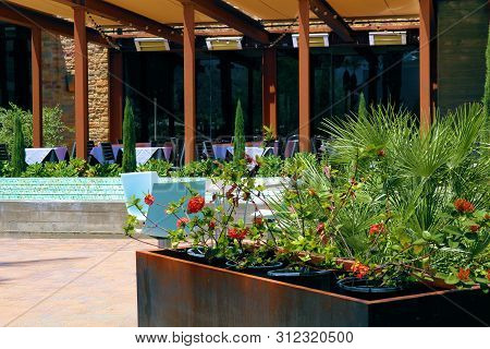 Restaurant With Outdoor Seating Surrounded By Manicured Plants And Flowers Taken In A Trendy Urban A