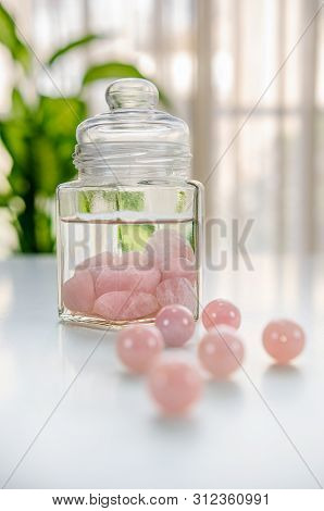 Burnished rose quartz stones are put inside of a glass jar. The drinking water is being charged with the healing energy of crystals. Six  beads are in the foreground out of focus. stock photo