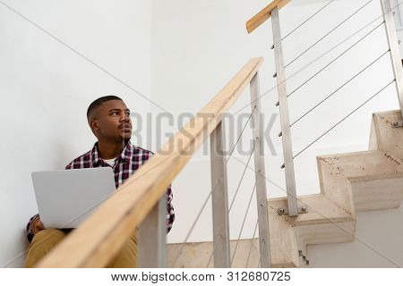 Front view of thoughtful African-american man looking away while working on laptop on stairs in a comfortable home. Authentic home lifestyle setting with young African American male stock photo