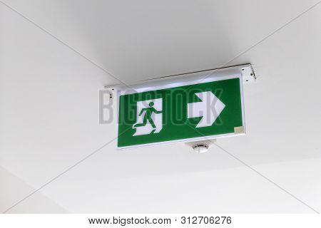 Fire Exit Sign. Emergency Fire Exit Door Exit Door On Ceiling. Green Emergency Exit Sign Showing The