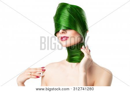 A close up portrait of a beautiful girl with a head rolled up in a leave posing in the studio over the white background. Beauty, nature, make up. stock photo