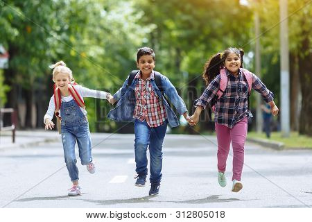 Back to school. Mixed Racial Group of happy elementary school students with backpacks running holding hands outdoors. Primary education concept. stock photo