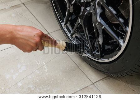 A male worker washes a black car with a special brush for cast wheels and scrubs the surface to shine in a vehicle detailing workshop. Auto service industry. stock photo