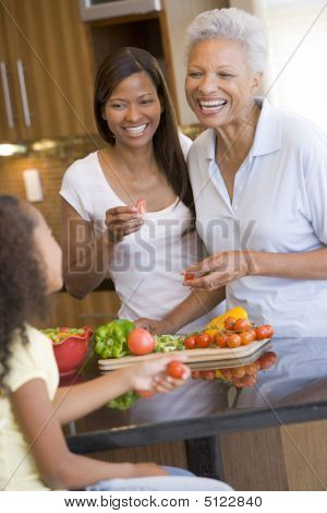 motherdaughterwomenEating Food Healthy Eating Home Cooking mealmealtime Preparing Food Smiling 30s 60s 9 Year Old African American Child Color Colour Cooking Daughter Elementary Age Enjoying Filipino Girl Happy Holding Home Image Indoors Kitchen Mid Adult stock photo