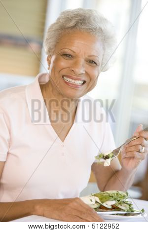 womanseniorDinner Enjoying Food Happy Healthy mealmealtimetimes Wine 60s African American Alcohol Casual Clothing Color Colour Domestic Domestic Life Enjoyment Healthy Eating Holding Home Home Cooking Image Indoors Inside Looking At Camera Lunch mealmealt stock photo