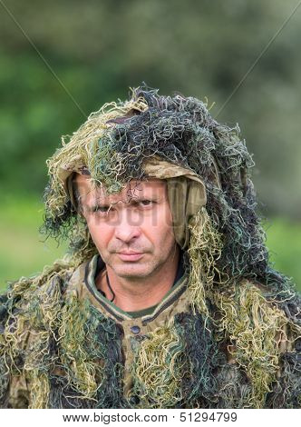 Portrait of man in camouflage ghillie suit stock photo