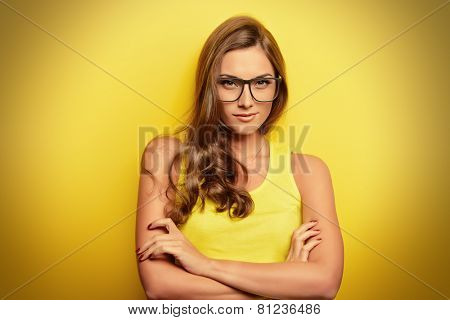 Beauty portrait of a happy young woman in spectacles and bright yellow dress over yellow background.
