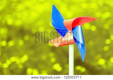 red and blue pinwheel. no wind conditions.motionless colorful pinwheel of four wings on a green blur background. copy space for your text stock photo