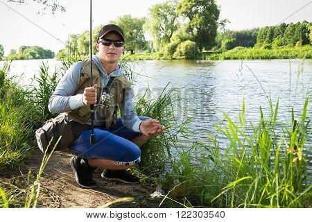 Fishing in river. A fisherman with a fishing rod on the river bank. Man fisherman catches a fish.Fishing, spinning reel, fish, Breg rivers. - The concept of a rural getaway. Article about fishing.