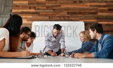 Group of colleagues having a brainstorming session in conference room. Young man explaining business plans to coworkers during meeting in boardroom.