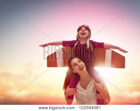 Mother and her child playing together. Little child girl plays astronaut. Child in an astronaut cost