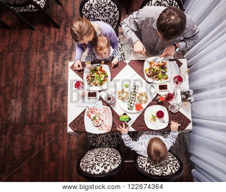 Family of four having meal at a restaurant, view from above